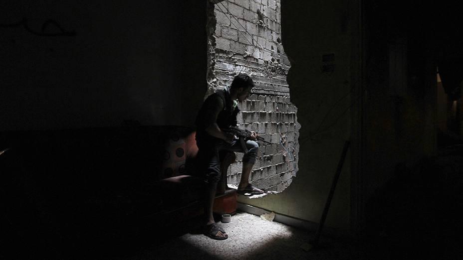 Um membro da brigada Shohadaa Badr, que opera sob o Exército Livre da Síria, olha através de um buraco na parede em Ashrafieh, Aleppo