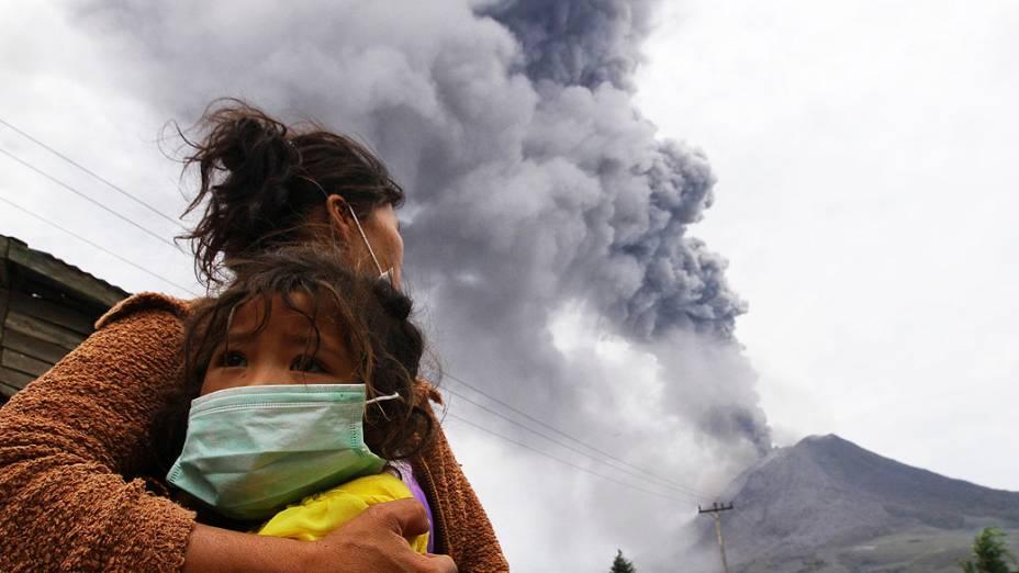 Mãe segura filha durante uma erupção do Monte Sinabung em Perteguhan, na Indonésia. Autoridades preparam abrigos temporários para os desabrigados