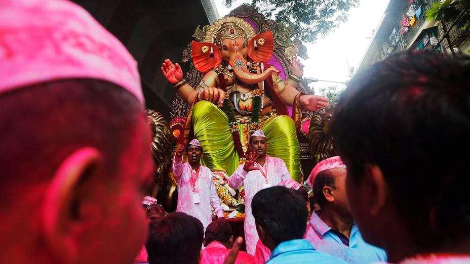 Devotos carregam um ídolo do deus hindu Ganesh, divindade da prosperidade, durante uma procissão pelas ruas, no último dia do festival Ganesh Chaturthi, em Mumbai, na Índia
