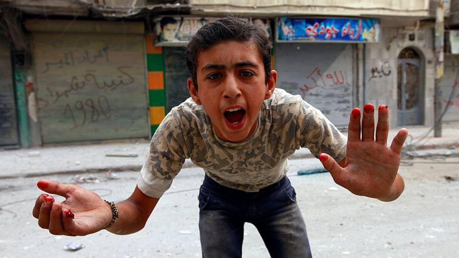 Menino exibe as mãos com sangue depois de um bombardeio por parte das forças leais ao presidente da Síria, Bashar al-Assad no bairro al-Myassar, em Aleppo