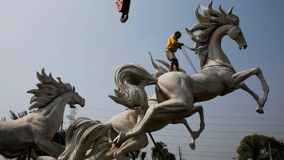 Homem trabalha na montagem de uma estátua de cavalos em um novo complexo habitacional em Parung, província de Java, na Indonésia