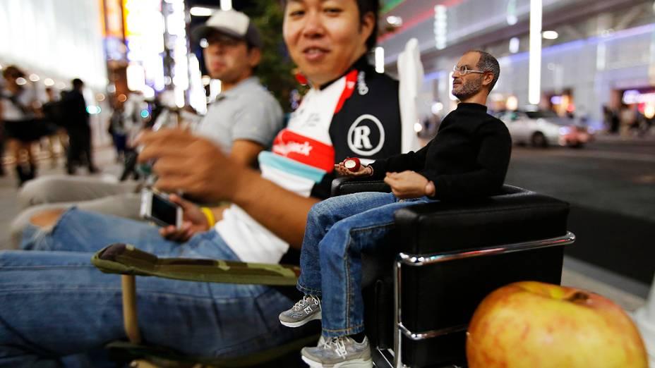 Pessoas se sentam ao lado de uma estatueta do co-fundador da Apple Steve Jobs enquanto esperam para o lançamento do novo iPhone 5S da Apple, no distrito comercial em Tóquio