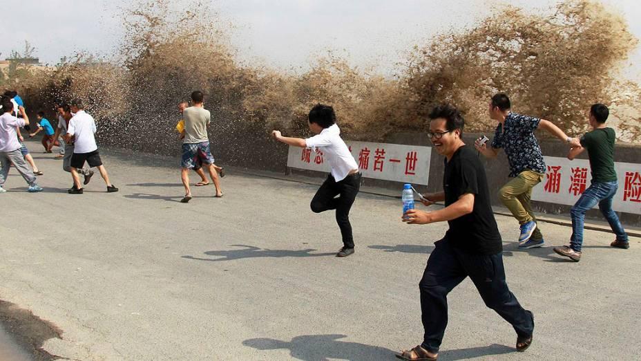 Turistas fogem de uma pororoca que atingiu uma barreira às margens do rio Qiantang em Hangzhou, província de Zhejiang, na China