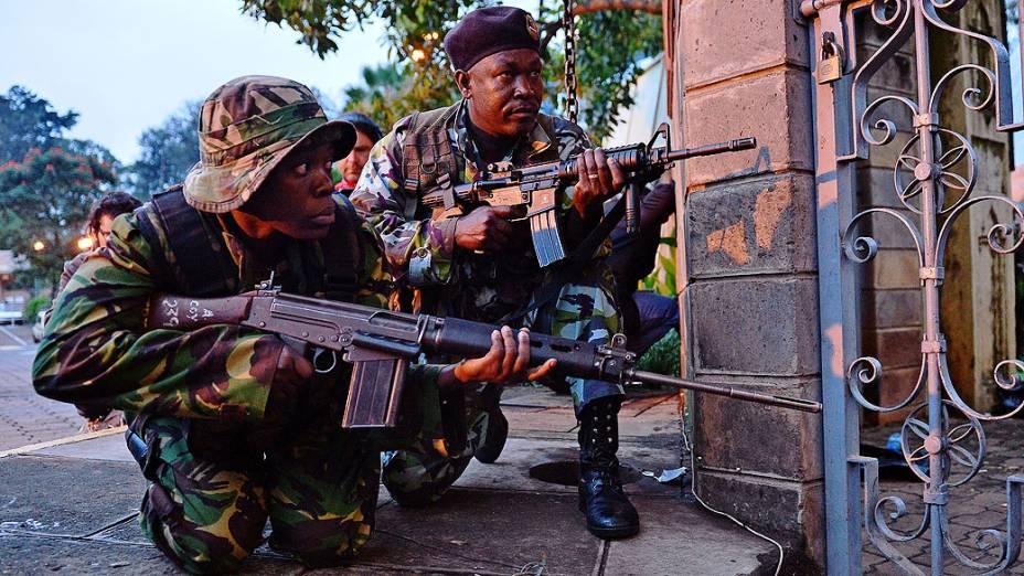 Soldados se escondem após tiroteio próximo ao shopping Westgate em Nairóbi. As tropas quenianas permanecem dentro do shopping em confronto com militantes do grupo terrorista somaliAl-Shabab, após granadas terem sido jogadas. Os terroristasameaçam matar os reféns que ainda estão no local