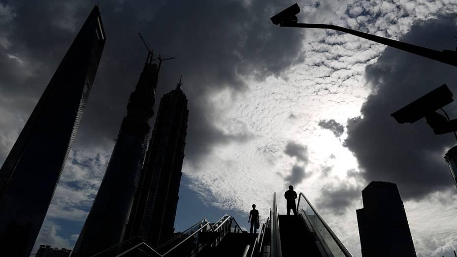 Pedestres usam um escada rolante, no distrito financeiro de Pudong, em Xangai, China