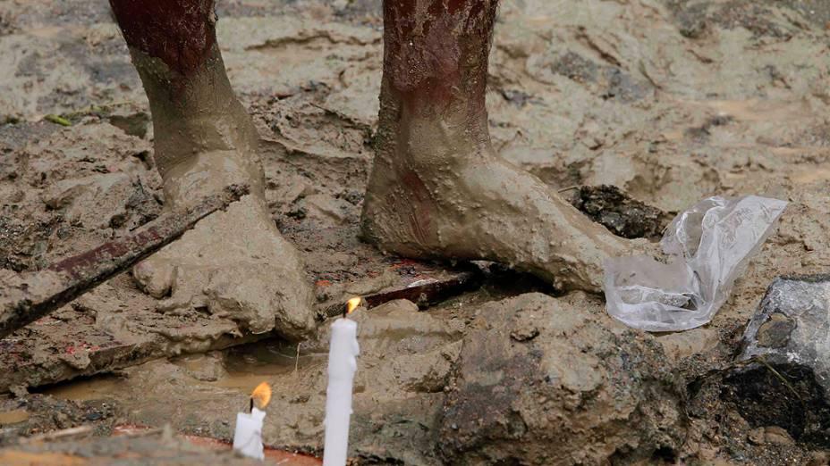 Morador acende velas para rezar por famílias que morreram depois que seus barracos foram cobertos pela lama em um deslizamento em Subic, norte das Filipinas, nesta terça-feira (24). Chuvas de monção atingiram a capital Manila e outras regiões
