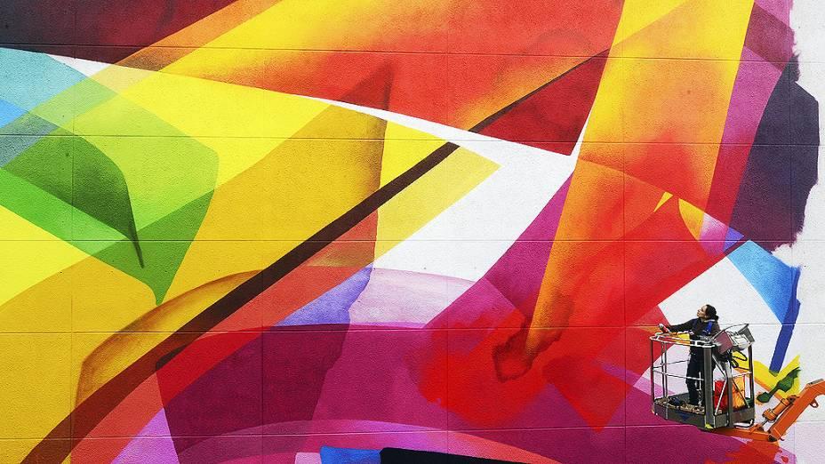 Artista alemã Claudia Walde faz os últimos retoques de sua obra em um mural gigantesco, na cidade alemã de Leipzig