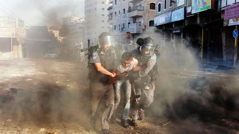 Policiais de fronteira israelenses detém um manifestante palestino durante confrontos no campo de refugiados de Shuafat na Cisjordânia, perto de Jerusalém