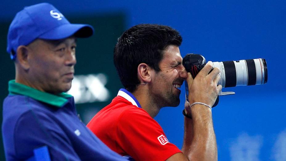 Novak Djokovic tira fotos com uma câmera durante uma partida beneficente com a chinesa Li Na para marcar a abertura do China Open Tennis Tournament, em Pequim