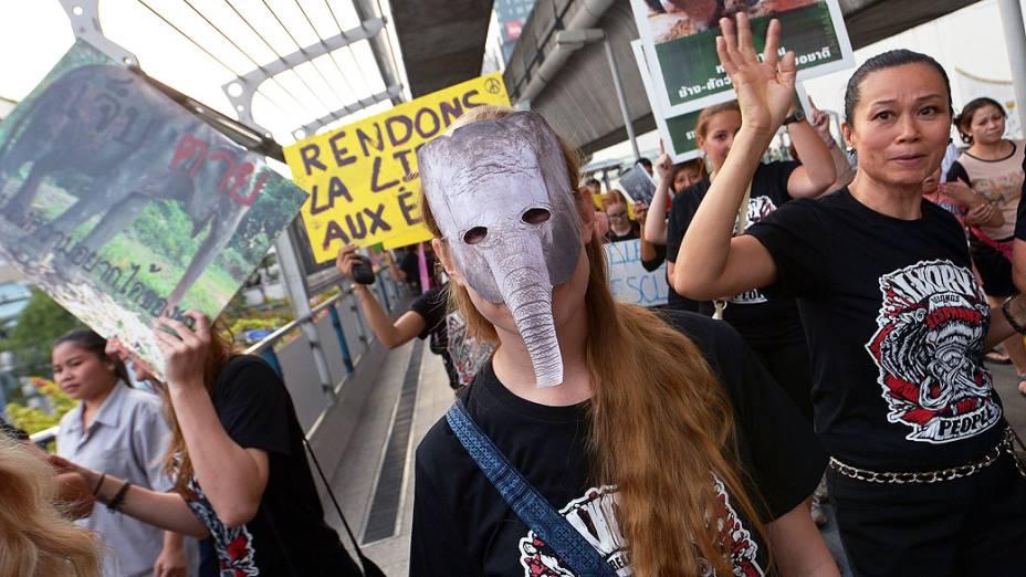 Ativista usa uma máscara de elefante durante a Marcha Internacional de Elefantes, em Bangcoc. Os ativistas chamam atenção para a conservação dos elefantes e uma proibição total do comércio de marfim ilegal