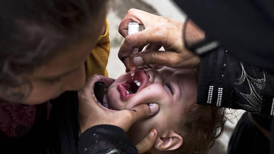 Médico dá uma vacina antipólio em Rawalpind. Uma bomba explodiu em Peshawar ao lado de uma van transportando guardas de segurança paquistanesas encarregados de proteger os trabalhadores envolvidos em uma unidade anti-poliomielite, no noroeste do Paquistão