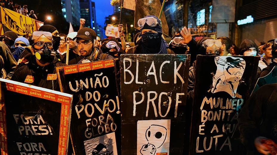 Manifestantes seguram cartazes durante um protesto de professores, exigindo melhores condições de trabalho e contra a violência da polícia no Rio de Janeiro
