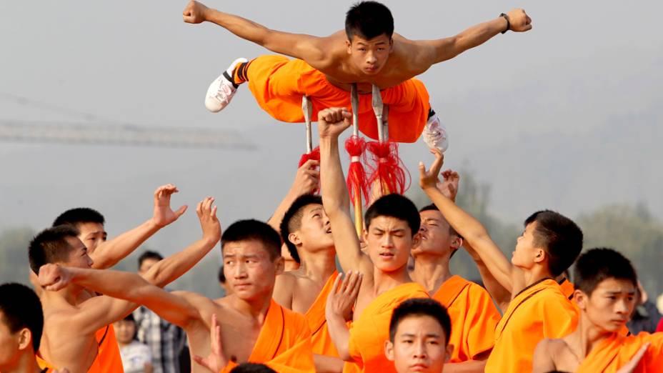 Menino é erguido por lanças, durante apresentação de estudantes de artes marciais shaolin, em um templo na China