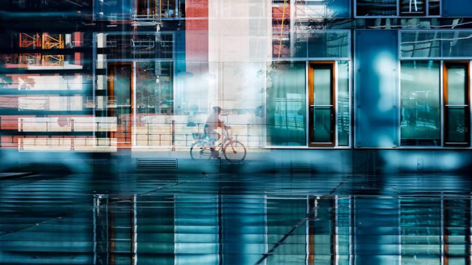 Uma pessoa anda de bicicleta ao longo do rio Spree, refletida pelas janelas de um prédio do parlamento de Berlim, na Alemanha
