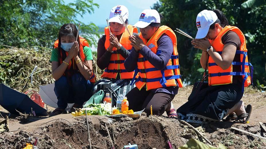 Parentes dos passageiros do acidente de avião da Lao Airlines fazem orações perto do local da tragédia que deixou 17 mortos, no Pakse, em Laos