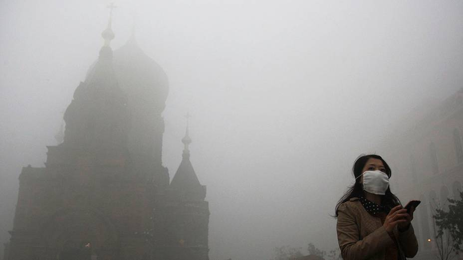Mulher usa máscara durante dia de forte poluição, no centro de Harbin, na China