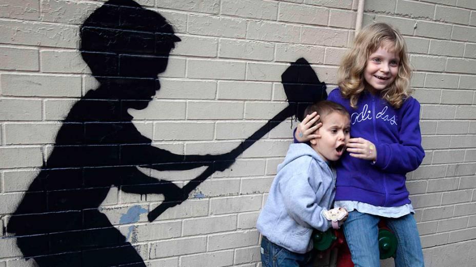 Crianças posam para uma foto em frente a um grafite do artista Banksy, em Nova York