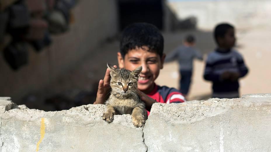 Menino brinca com seu gato em uma casa abandonada, na Faixa de Gaza