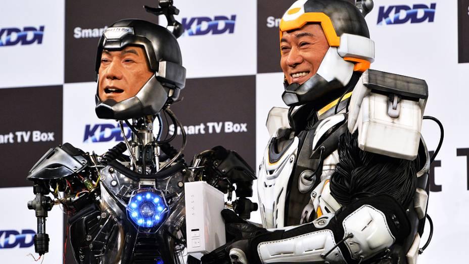 Com uma roupa robótica, o ator japonês Ken Matsudaira posa ao lado de um robô feito à sua semelhança em uma coletiva de imprensa em Tóquio, no Japão