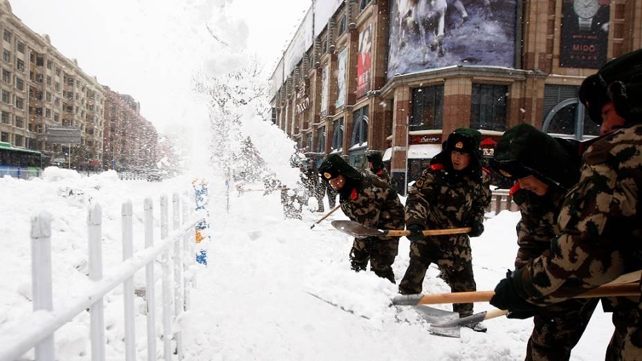 Soldados retiram neve de uma rua na cidade de Harbin, província de Heilongjiang, durante pior tempestade de neve dos últimos 50 anos, na China