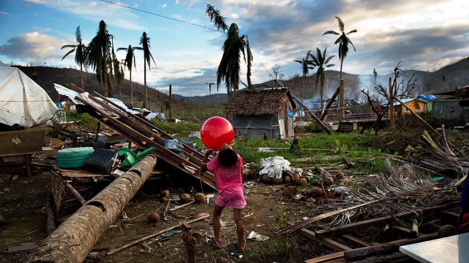 Menina brinca com uma bola nos escombros onde a casa de sua família foi arrasada por um coqueirodurante o tufão Haiyan, nos arredores de Tacloban, nas Filipinas