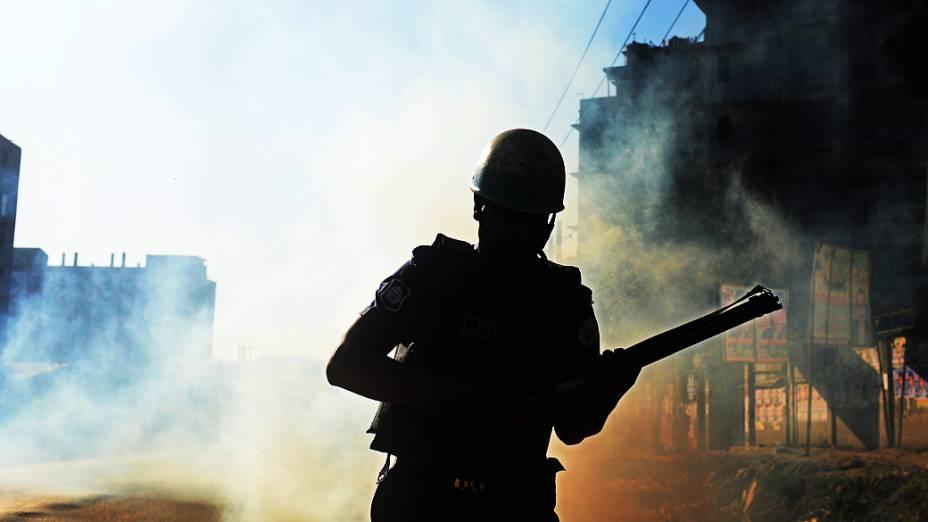 Policial da tropa de choque de Bangladesh recarrega arma em confronto com manifestantes, nesta terça-feira (19)