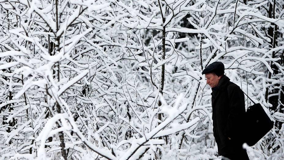 Homem caminha por árvores cobertas de neve em uma estação de trem nos arredores de Moscou, Rússia