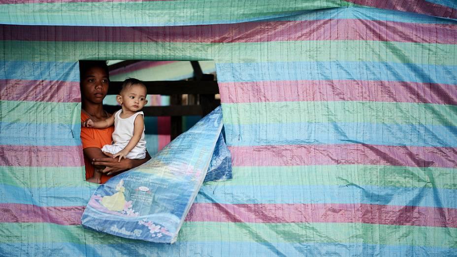 Mulher segura um bebê no colo em uma casa improvisada na baía de Tacloban, na província de Leyte, região devastada pela passagem do supertufão Haiyan, nas Filipinas
