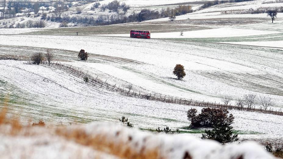Ônibus transita em umcampo coberto de neve nos arredores da cidade deSkopje, na Macedônia