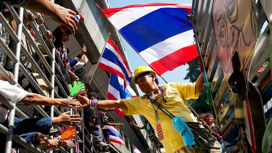 Manifestantes cumprimentam uns aos outros de cima de caminhões durante uma manifestação em frente à sede da polícia central de Bangcoc, na Tailândia. Os manifestantes continuaram seus protestos após vários dias de violentos confrontos com a polícia