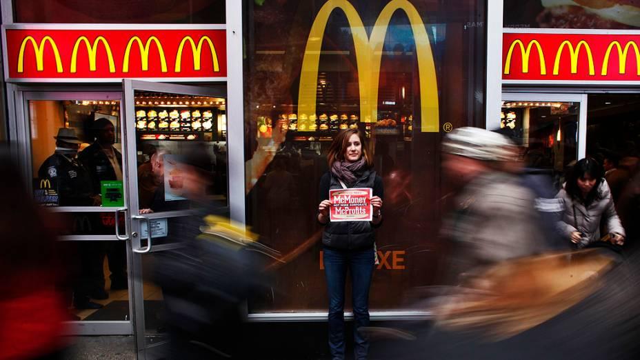 Representante do grupo MoveOn segura um cartaz durante protesto em frente a um restaurante McDonalds na Times Square, em Nova York. O grupo faz uma petição, endereçada às grandes redes de fast food exigindo um salário digno para todos os funcionários do setor