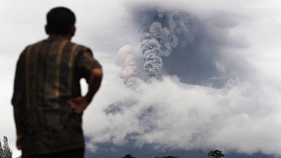Homem observa a fumaça expelida pelo Monte Sinabung durante uma erupção em Gundaling, Norte de Sumatra, na Indonésia