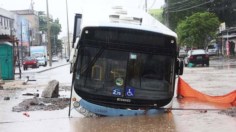 Ônibus cai em buraco na manhã desta quarta-feira (11), durante alagamento na Avenida Vicente de Carvalho na Penha, na zona norte do Rio de Janeiro