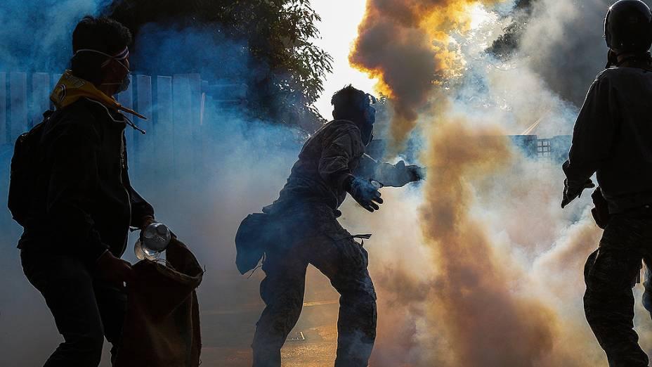 Manifestante de oposição ao governo atira uma bomba de gás lacrimogêneo em direção aos policiais durante confrontos no centro de Bangcoc, na Tailândia