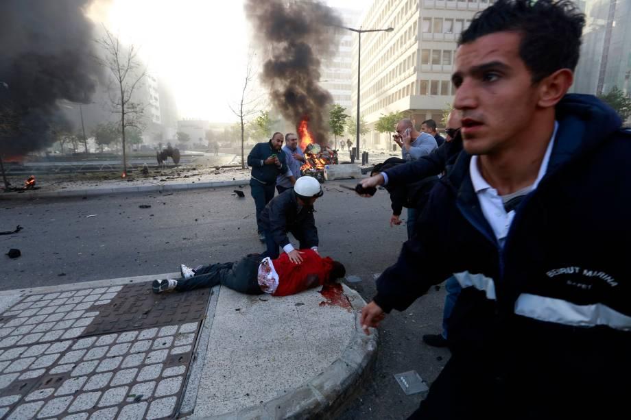 Pessoas correram para ajudar um homem ferido no local de uma explosão no centro da cidade de Beirute, no Líbano