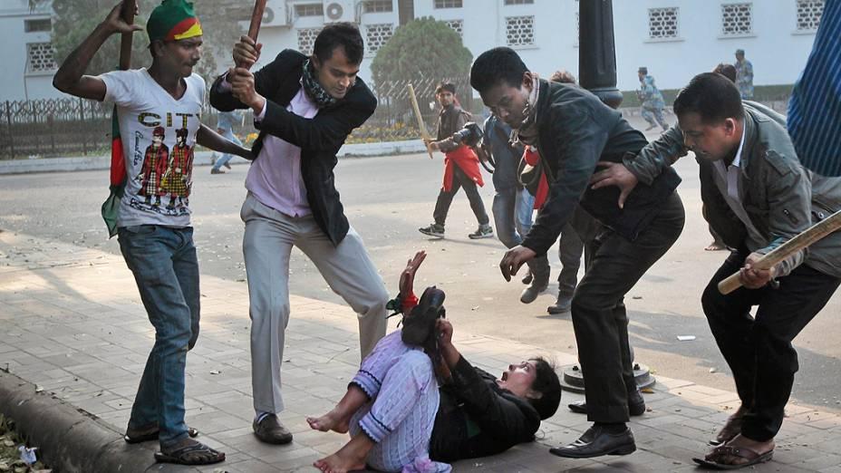 Defensores da Awami League, partido da situação em Bangladesh agridem uma mulher ligada ao principal partido de oposição do país, o Partido Nacionalista de Bangladesh (BNP), durante um protesto de ativistas da oposição em Daca