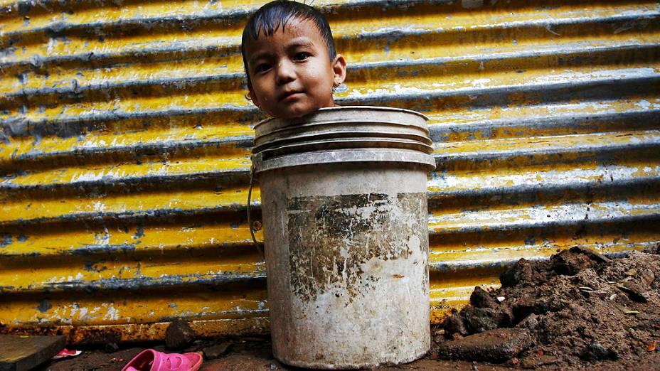 Um menino aguarda por sua mãe dentro de um balde enquanto espera para tomar banho em uma cabana improvisada na cidade indiana de Chennai