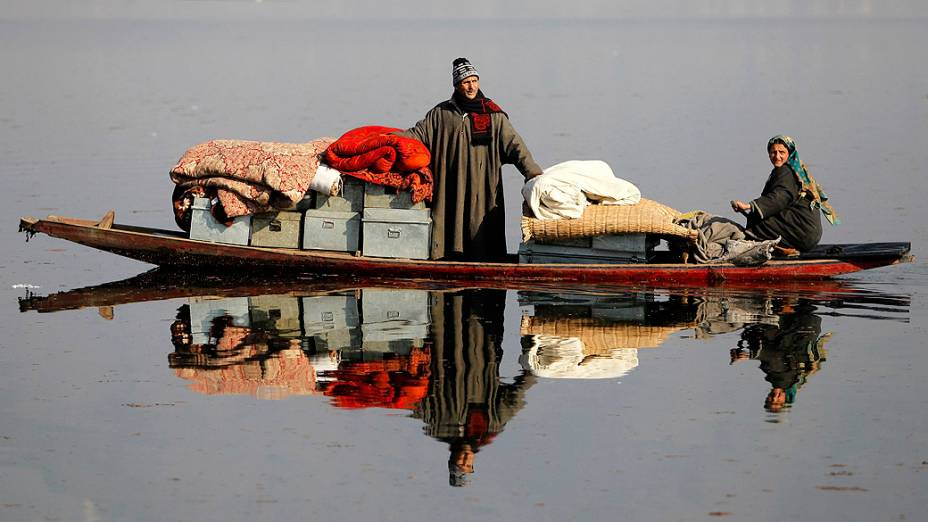 Homem transporta seus pertences em uma canoa após ter sua casa destruída por um incêndio em Dhobi Ghat, nos arredores de Srinagar, na região da Caxemira administrada pela Índia