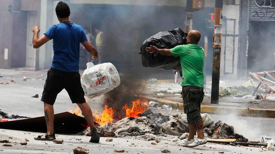 Homens ateiam fogo em sacos de lixo durante protesto contra a falta de energia que tem afetado a cidade de Buenos Aires há duas semanas