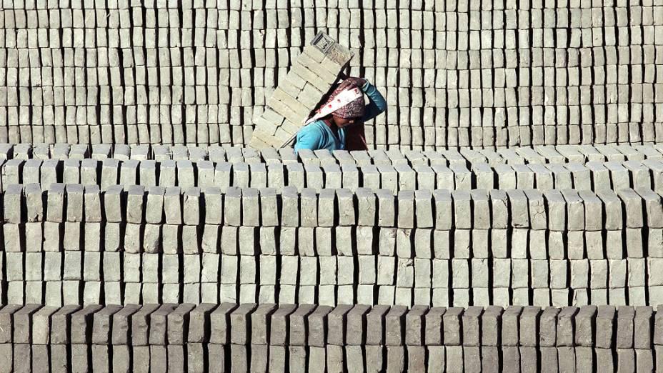 Mulher carrega uma pilha de tijolos durante o dia de trabalho em Lalitpur, Nepal
