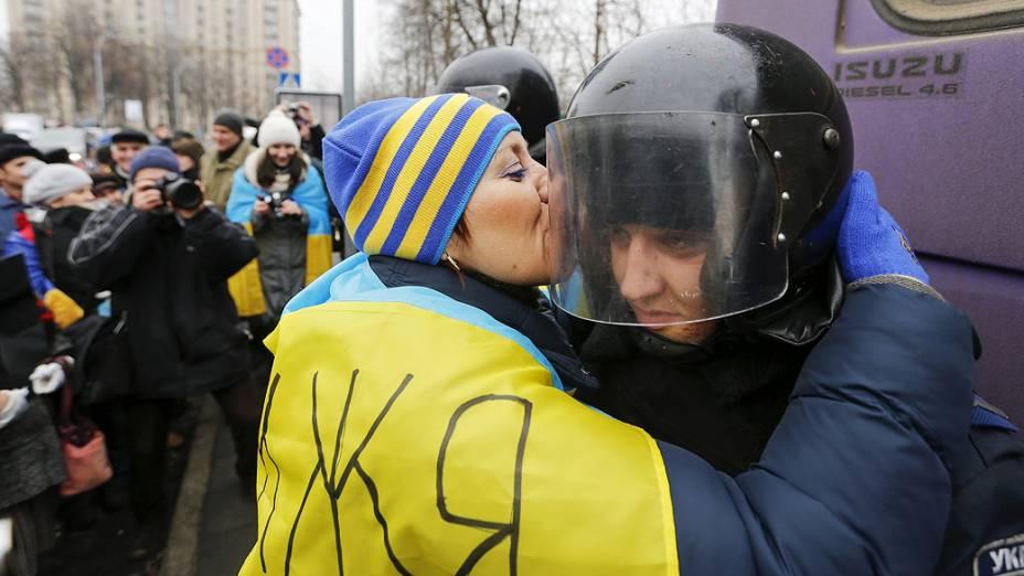 Manifestante pró União Europeia beija o capacete de um policial durante protesto em Kiev