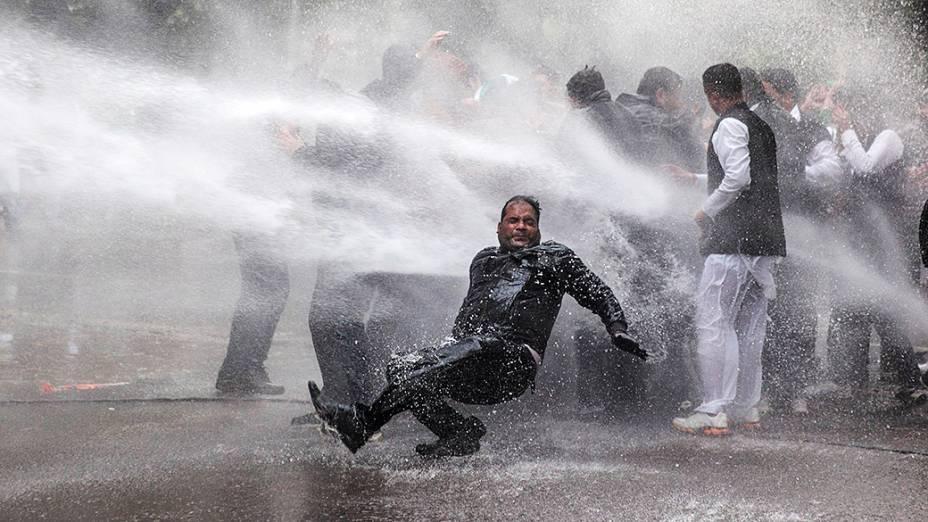 Ativista do partido de oposição indiano Bharatiya Janata atingido por um jato de água disparado pela polícia durante um protesto em frente a residência do vice-presidente do Congresso, Rahul Gandhi, em Nova Délhi