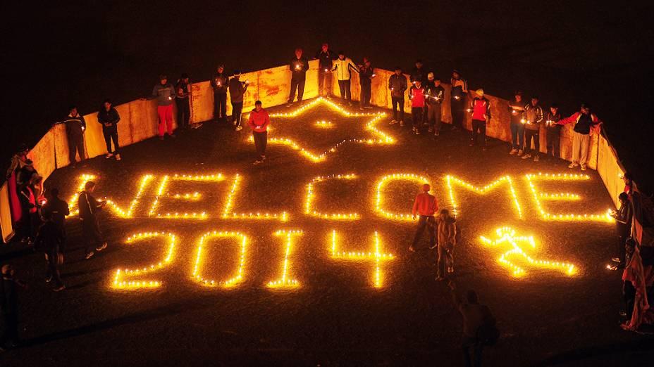 Jogadores indianos acendem velas durante um evento para receber o Ano Novo, em Allahabad, na Índia