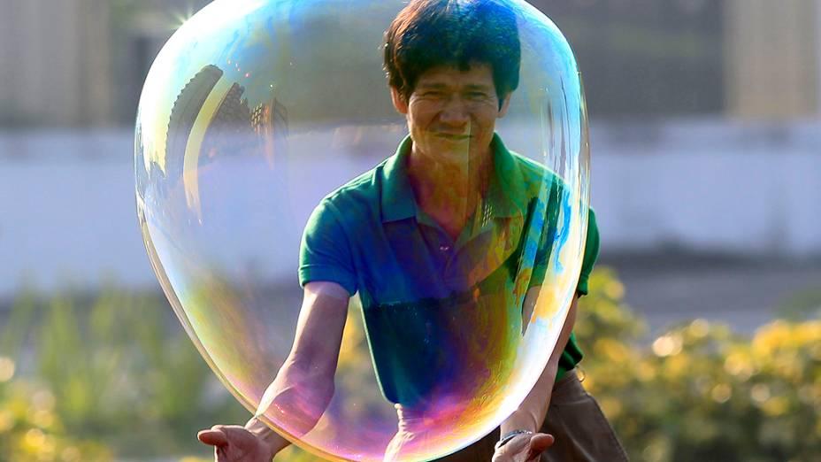 Um homem brinca com uma bolha ao comemorar o dia de Ano Novo em um parque em Manila, nas Filipinas