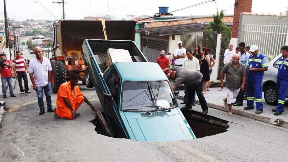 Um carro caiu dentro de uma cratera que se abriu na Rua Pernambuco, em Itapecerica da Serra, SP, na manhã da quinta-feira (02)