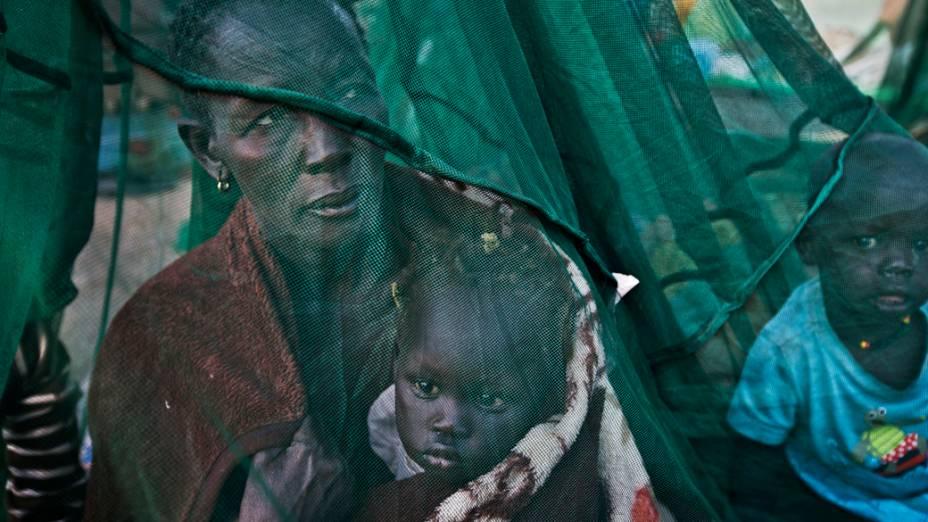 Família refugiada do recente conflito entre o governo e forças rebeldes em busca de abrigo na cidade de Awerial, no Sudão do Sul na quinta-feira (02)