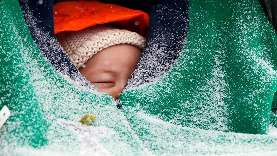 Bebê de dois meses de idade, tirou um cochilo abrigado em seu cobertor enquanto a neve caía em Boston, na quinta-feira (02)
