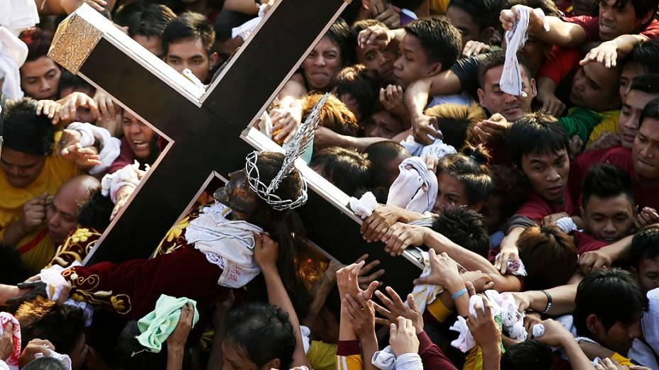 Católicos filipinos sobem em carro para tentar tocar a imagem do Nazareno Negro, nesta quinta-feira (9), em Manila. A imagem, feita de madeira e retratando Jesus Cristo negro, foi levada para o país por missionários espanhóis do México em 1906, num ritual que acontece todos os anos