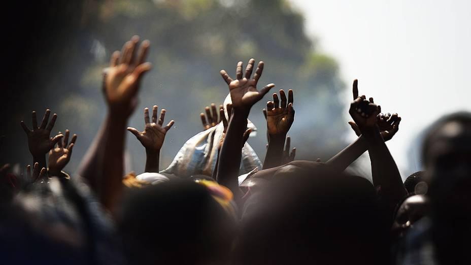 Pessoas levantam as mãos esperando distribuição de comida, na cidade de Bangui, República Centro Africana