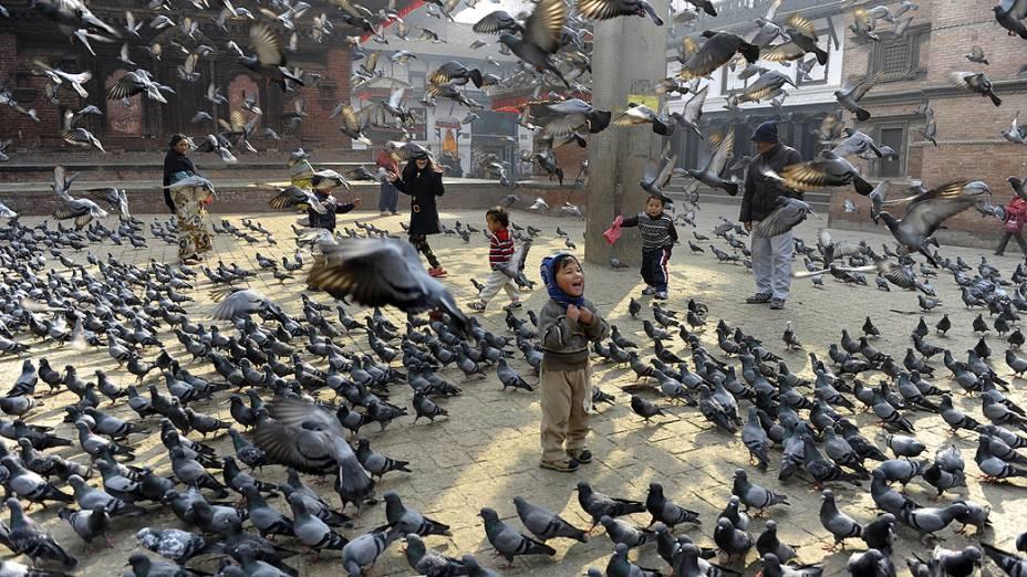 Crianças alimentam pombos na Praça Durbar em Katmandu, no Nepal. O local está na lista de patrimônios mundiais da Unesco